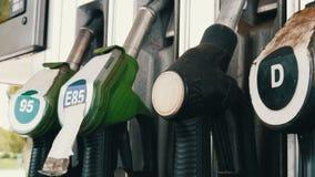 Verschiedene alte Brennstoffaufnahmepistolen für strömenden Benzinfall in der Reihe an der Tankstelle Benzin- oder Tankstellegasb stock footage