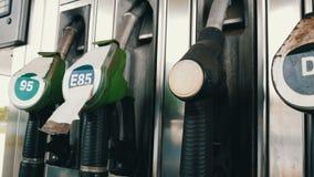 Verschiedene alte Brennstoffaufnahmepistolen für strömenden Benzinfall in der Reihe an der Tankstelle Benzin- oder Tankstellegasb stock video