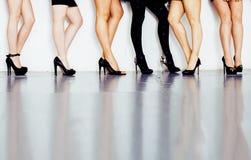 Verschiedene Art Paar von Frauenbeinen in der Höhe folgt schwarzen Schuhen auf weißem Hintergrund und Boden, Verschiedenartigkeit lizenzfreies stockbild