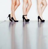 Verschiedene Art Paar von Frauenbeinen in der Höhe folgt schwarzen Schuhen auf weißem Hintergrund und Boden, Verschiedenartigkeit lizenzfreie stockbilder
