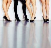Verschiedene Art Paar von Frauenbeinen in der Höhe folgt schwarzen Schuhen auf weißem Hintergrund und Boden, Verschiedenartigkeit stockfoto