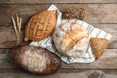 Verschiedene Arten des frischen Brotes auf Holztisch lizenzfreie stockbilder
