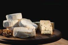 Verschiedene Arten des Käses auf einem hölzernen Hintergrund verschiedene Käse auf einer hölzernen Platte Stockfotografie