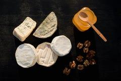 Verschiedene Arten des Käses auf einem hölzernen Hintergrund verschiedene Käse auf einem schwarzen Hintergrund Stockfoto