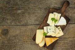 Verschiedene Arten des Käses auf einem hölzernen Schneidebrett Lokalisierung auf dem Weiß Milchverarbeitung Nähren Sie Nahrung Lizenzfreie Stockfotografie