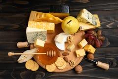 Verschiedene Arten des Käses auf einem rustikalen Holztisch lizenzfreies stockfoto