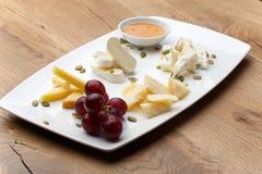 Verschiedene Arten des Käses mit Honig und Trauben Stockbild