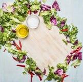 Verschiedene Arten des Kopfsalates zeichneten Rahmen um Schneidebrett, Öl und Salz, Platz für Text Stockfoto