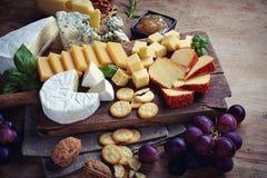 Verschiedene Arten des Käses auf einem hölzernen Hintergrund Stockfotografie