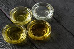 Verschiedene Arten des Pflanzenöls in den Glasschüsseln Stockfotos