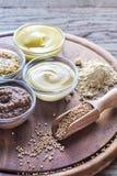 Verschiedene Arten des Senfes auf dem hölzernen Hintergrund Stockfotos