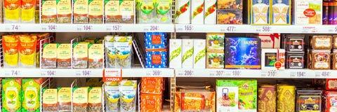 Verschiedene Arten des Tees auf den Ladenregalen Text auf russisch: grün, azurblau stockfotos