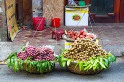 Verschiedene Arten von den Früchten, die von den traditionellen hängenden Körben verkaufen, können in Hanoi finden Stockbild