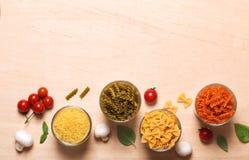Verschiedene Arten von italienischen Teigwaren mit Gemüse auf dem Tisch Lizenzfreie Stockfotos