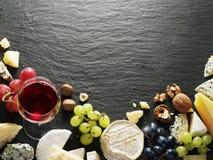 Verschiedene Arten von Käsen mit Weinglas und -früchten Stockfoto
