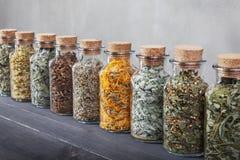 Verschiedene Arten von Kräutern für Tee innerhalb der Glasflaschen Stockbilder