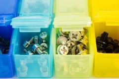 Verschiedene Arten von Schrauben in den kleinen farbigen Plastikbehältern V Stockbilder