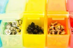 Verschiedene Arten von Schrauben in den kleinen farbigen Plastikbehältern V Stockbild