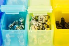 Verschiedene Arten von Schrauben in den kleinen farbigen Plastikbehältern V Stockfotografie