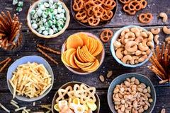 Verschiedene Arten von Snäcken - Chips, gesalzene Erdnüsse, Acajoubäume, Erbsen mit Wasabi, Brezeln mit Salz, Kartoffeln, gesalze Lizenzfreies Stockbild
