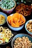Verschiedene Arten von Snäcken - Chips, gesalzene Erdnüsse, Acajoubäume, Erbsen mit Wasabi, Brezeln mit Salz, Kartoffeln, gesalze Stockbild