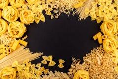 Verschiedene Arten von Teigwaren auf dem schwarzen Hintergrund Lizenzfreies Stockbild