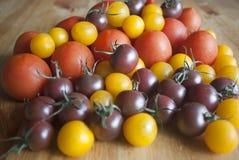 Verschiedene Arten von Tomaten auf hölzernem Hintergrund Lizenzfreies Stockfoto