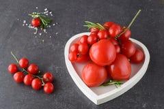 Verschiedene Arten von Tomaten auf Niederlassungen im Herzen formten Behälter auf einem dunkelgrauen abstrakten Hintergrund Lizenzfreie Stockfotografie