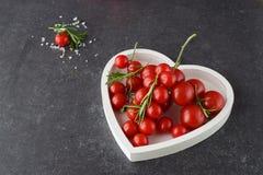 Verschiedene Arten von Tomaten auf Niederlassungen im Herzen formten Behälter auf einem dunkelgrauen abstrakten Hintergrund Raum  Stockbilder