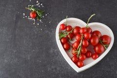 Verschiedene Arten von Tomaten auf Niederlassungen im Herzen formten Behälter auf einem dunkelgrauen abstrakten Hintergrund Raum  Stockfotografie