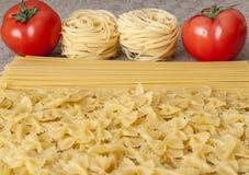 Verschiedene Arten von ungekochten Teigwaren und von Tomate Lizenzfreie Stockbilder