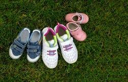 Verschiedene Babyschuhe drei Paare im Gras - das Symbol der Kinder von einer großen Familie Konzept Kopieren Sie Platz Lizenzfreies Stockbild