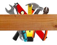 Verschiedene Bauwerkzeuge und hölzerne Planke Lizenzfreies Stockfoto