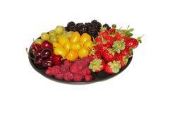 Verschiedene Beeren auf der Platte Stockfoto