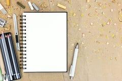 Verschiedene Bleistifte und bunte Kreiden mit offenem leerem Notizblock an Lizenzfreie Stockbilder