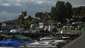 Verschiedene Boote, Yachten und Motorboote werden am Pier verankert, der um im Fjord eingezäunt wird Im Hintergrund gibt es majes Lizenzfreie Stockfotos