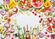 Verschiedene bunte geschnittene Früchte, Beeren, Gemüse, Kräuter, gossen Wasser in den Flaschen auf weißem Hintergrund, Draufsich lizenzfreies stockbild