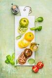Verschiedene bunte geschnittene Tomaten auf weißem Marmorschneidebrett Stockbilder