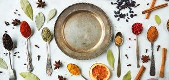 Verschiedene bunte indische Gewürze und Kräuter in den silbernen Löffeln auf weißem Hintergrund Stockbilder