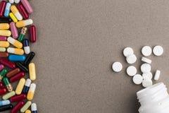 Verschiedene bunte Kapseln und Tablettenfläschchen von den weißen runden Pillen Lizenzfreie Stockfotos