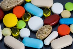 Verschiedene bunte Pillen auf schwarzem Hintergrund Lizenzfreie Stockfotos