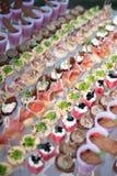 Verschiedene Canapes mit geräuchertem Lachs, Gurke und roter Johannisbeere dienten auf Seeoberteil über einer Spiegelplatte Frisc stockfotografie