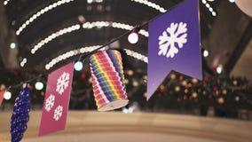 Verschiedene Dekorationen, die am Draht mit Lampen innerhalb des Kaufhauses hängen stock video