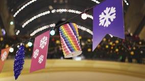 Verschiedene Dekorationen, die am Draht mit Lampen innerhalb des Kaufhauses hängen stock footage