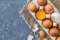Verschiedene Eier im Karton verpacken auf dunkler Steintabelle Stockfotografie