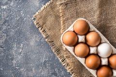 Verschiedene Eier im Karton verpacken auf dunkler Steintabelle Lizenzfreie Stockbilder