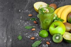 Verschiedene exotische Früchte und grünes Cocktail von der Kiwi auf einem dunkelgrauen Steinhintergrund Organische Bestandteile f Stockfoto