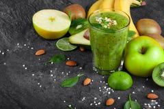 Verschiedene exotische Früchte und grünes Cocktail von der Kiwi auf einem dunkelgrauen Steinhintergrund Organische Bestandteile f Stockfotos