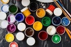 Verschiedene Farben in den Banken, in den pensils und in den Bürsten auf dem flo Lizenzfreie Stockfotos