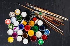 Verschiedene Farben in den Banken, in den pensils und in den Bürsten auf dem flo Stockbilder